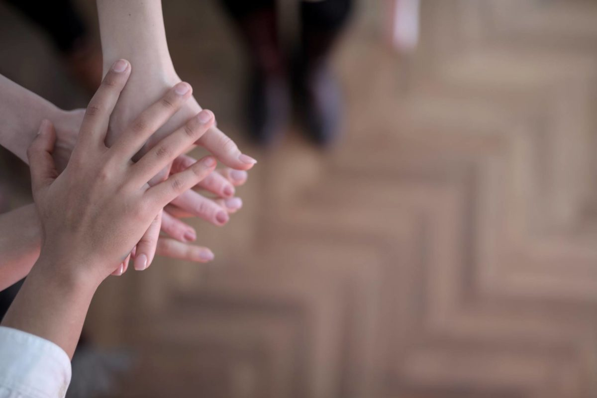 crop group stacking hands together