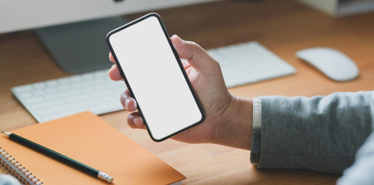 person leaning on wooden table using smartphone