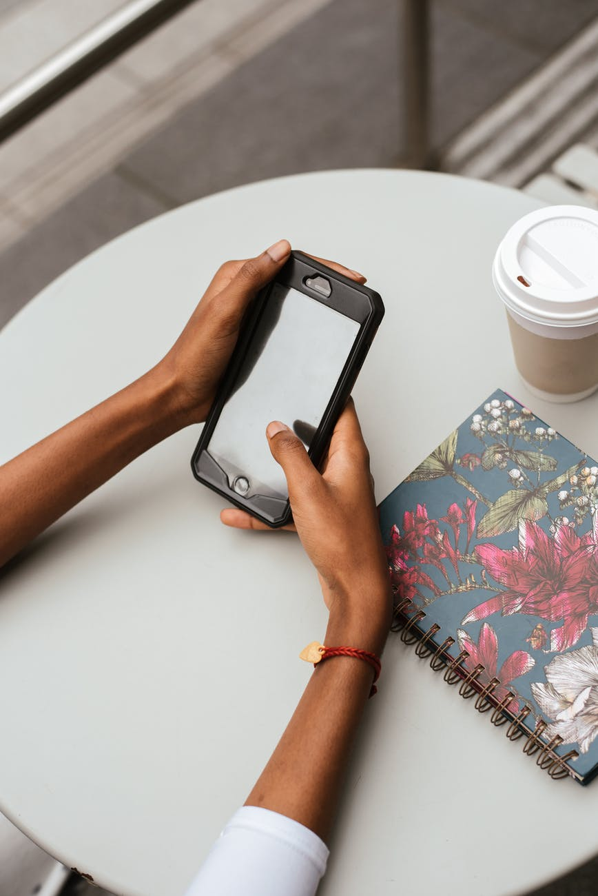 crop ethnic woman chatting on smartphone at cafe table