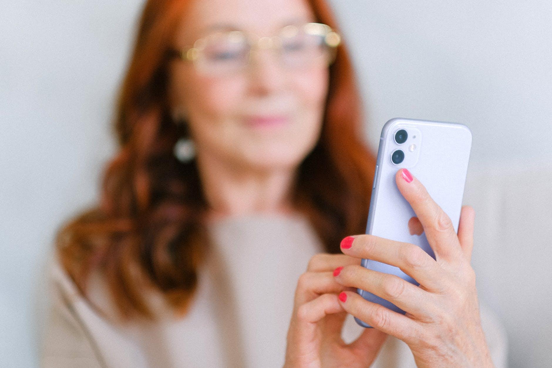 elderly woman messaging on modern smartphone