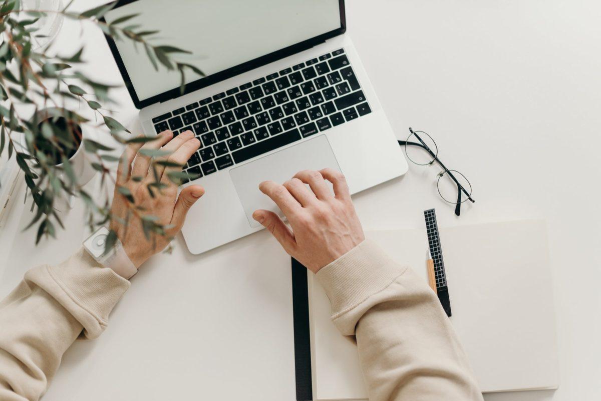 person in beige long sleeve shirt using macbook pro