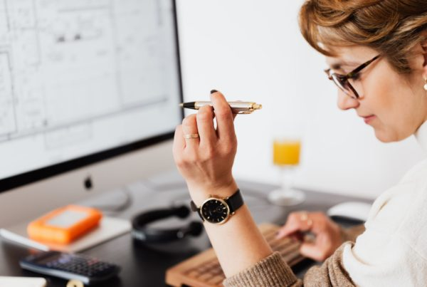 pen in hand of female typing on computer during work in office